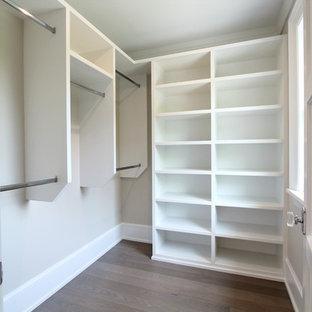 Modelo de armario vestidor unisex, clásico renovado, pequeño, con armarios abiertos, puertas de armario blancas, suelo de madera en tonos medios y suelo marrón