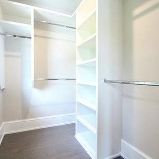 Diseño de armario vestidor unisex, actual, pequeño, con armarios abiertos, puertas de armario blancas, suelo de madera en tonos medios y suelo marrón