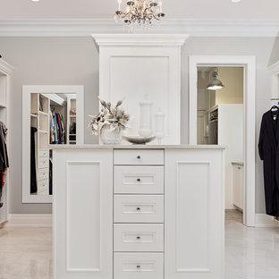 Modelo de armario vestidor unisex, clásico renovado, grande, con puertas de armario blancas, suelo de baldosas de porcelana, suelo beige y armarios con paneles empotrados