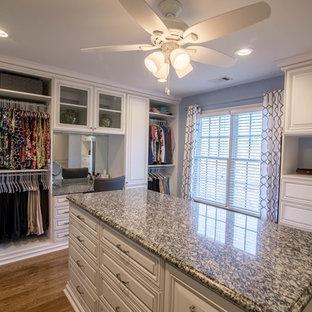 Diseño de armario vestidor unisex, tradicional, grande, con puertas de armario blancas, suelo marrón, armarios con paneles con relieve y suelo de madera en tonos medios