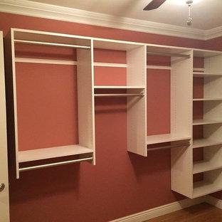 Imagen de armario vestidor unisex, moderno, de tamaño medio, con armarios con paneles lisos, puertas de armario blancas y suelo de madera clara