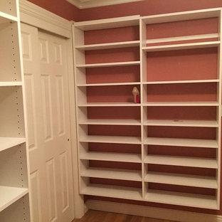 Diseño de armario vestidor unisex, minimalista, de tamaño medio, con armarios con paneles lisos, puertas de armario blancas y suelo de madera clara