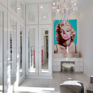 Foto på ett stort vintage omklädningsrum för kvinnor, med luckor med glaspanel, vita skåp, marmorgolv och vitt golv