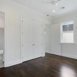 Ejemplo de armario unisex, tradicional, pequeño, con armarios con paneles lisos, puertas de armario blancas y suelo de madera oscura