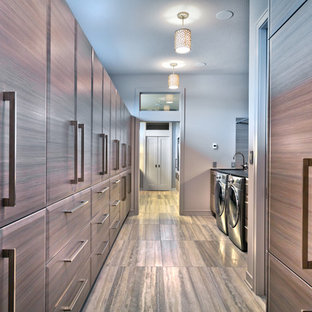 Expansive contemporary gender neutral walk-in wardrobe in Minneapolis with flat-panel cabinets, grey cabinets, travertine flooring and grey floors.