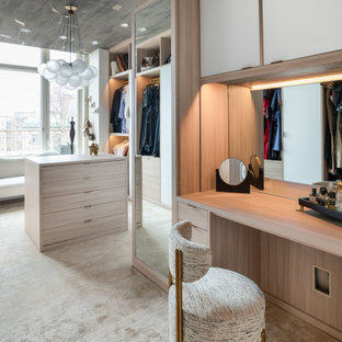 Geräumiges Modernes Ankleidezimmer mit Ankleidebereich, flächenbündigen Schrankfronten, hellen Holzschränken, Teppichboden, beigem Boden und Tapetendecke in New York