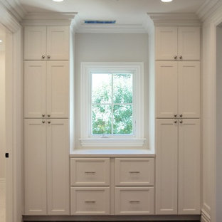 Mid-sized elegant gender-neutral medium tone wood floor and brown floor reach-in closet photo in San Francisco with shaker cabinets and white cabinets