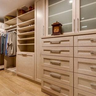 Modelo de armario vestidor de hombre, actual, grande, con armarios tipo vitrina, puertas de armario de madera clara, suelo de baldosas de porcelana y suelo beige