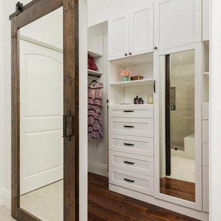 Modelo de vestidor unisex, tradicional, grande, con armarios estilo shaker, puertas de armario blancas, suelo de madera en tonos medios y suelo marrón