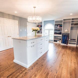 Diseño de vestidor unisex, tradicional, grande, con suelo de madera en tonos medios, suelo marrón, armarios estilo shaker y puertas de armario blancas