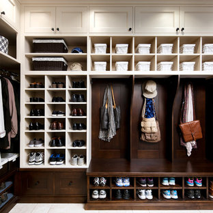 This is an example of a large traditional gender neutral walk-in wardrobe in Toronto with beige cabinets, open cabinets and travertine flooring.