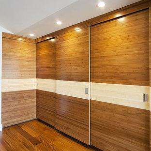 Ejemplo de vestidor unisex, contemporáneo, grande, con armarios con paneles lisos, puertas de armario de madera oscura y suelo de madera en tonos medios