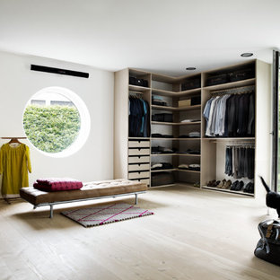 This is an example of a large scandinavian gender-neutral dressing room in Aarhus with open cabinets, light wood cabinets, light hardwood floors and beige floor.