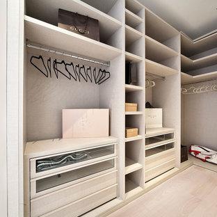 Bild på ett mellanstort funkis walk-in-closet för könsneutrala, med släta luckor, skåp i slitet trä, ljust trägolv och beiget golv