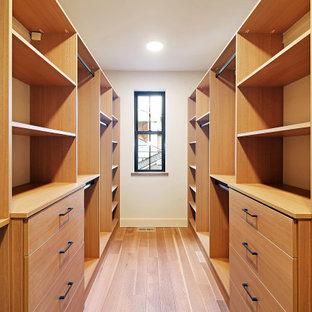 Diseño de armario vestidor unisex, nórdico, grande, con armarios con paneles lisos, puertas de armario de madera oscura, suelo de madera en tonos medios y suelo marrón
