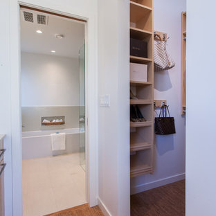 Aménagement d'un petit dressing contemporain neutre avec un placard sans porte, des portes de placard en bois clair et un sol en liège.