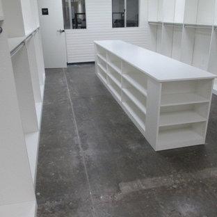Esempio di un grande spazio per vestirsi unisex moderno con ante lisce, ante bianche, pavimento in cemento e pavimento grigio
