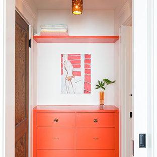 Modern inredning av en garderob, med mellanmörkt trägolv, släta luckor och orange skåp
