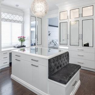 Imagen de vestidor de mujer, clásico renovado, con puertas de armario blancas, suelo de madera oscura y suelo marrón