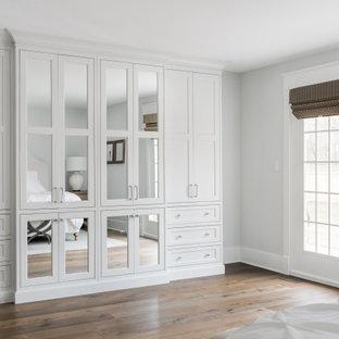 Cette photo montre une armoire encastrée nature de taille moyenne et neutre avec un placard à porte plane, des portes de placard blanches, un sol en bois brun et un sol marron.