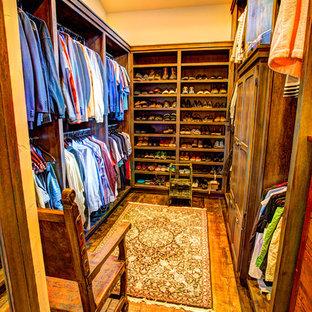 Foto de armario vestidor unisex, rústico, grande, con armarios con paneles lisos, puertas de armario con efecto envejecido y suelo de madera en tonos medios