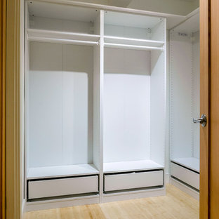 Photo of a large arts and crafts gender-neutral walk-in wardrobe in Vancouver with white cabinets and bamboo floors.