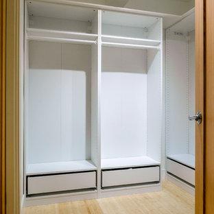 Amerikansk inredning av ett stort walk-in-closet för könsneutrala, med vita skåp och bambugolv