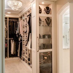 Ejemplo de armario vestidor de mujer, tradicional, de tamaño medio, con armarios tipo vitrina, puertas de armario de madera clara, moqueta y suelo beige