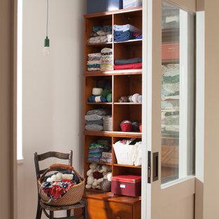 Imagen de armario y vestidor escandinavo con armarios abiertos, puertas de armario de madera oscura, suelo de madera en tonos medios y suelo marrón