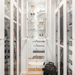 Ejemplo de armario vestidor de mujer, tradicional renovado, con armarios estilo shaker, puertas de armario blancas, suelo de madera en tonos medios y suelo marrón
