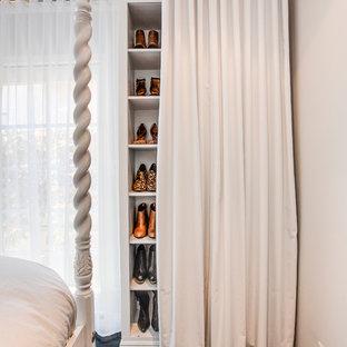 Idée de décoration pour un placard dressing tradition pour une femme avec un placard sans porte, des portes de placard blanches et un sol en bois foncé.