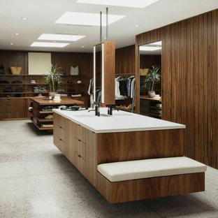 フェニックスの広いサンタフェスタイルのおしゃれな収納・クローゼット (フラットパネル扉のキャビネット、濃色木目調キャビネット、コンクリートの床、グレーの床) の写真