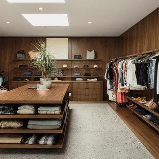 Diseño de vestidor de estilo americano, grande, con puertas de armario de madera en tonos medios, suelo de cemento y suelo gris