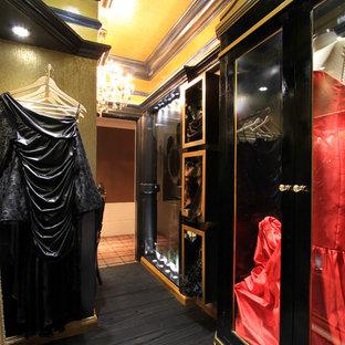 Foto di un piccolo spazio per vestirsi per donna bohémian con ante di vetro, ante nere e parquet scuro