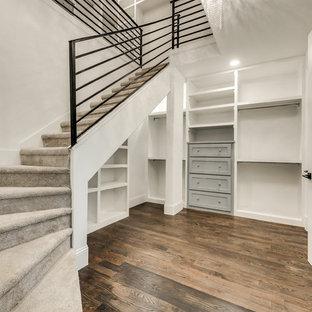 Modelo de armario vestidor unisex, clásico renovado, grande, con armarios con paneles empotrados, puertas de armario grises, suelo de madera en tonos medios y suelo marrón
