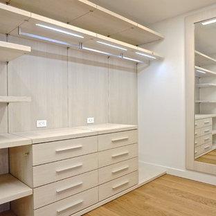 Diseño de armario vestidor unisex, minimalista, grande, con armarios con paneles lisos, puertas de armario de madera clara y suelo de madera en tonos medios