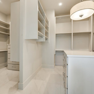 Inspiration for a large modern gender-neutral walk-in wardrobe in Dallas with louvered cabinets, white cabinets, marble floors and white floor.