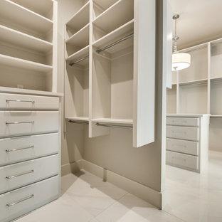 Diseño de armario vestidor unisex, minimalista, grande, con armarios con puertas mallorquinas, puertas de armario blancas, suelo de mármol y suelo blanco