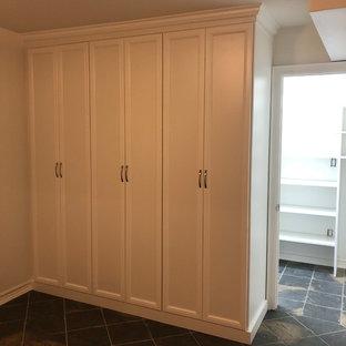 Ejemplo de armario unisex, tradicional, de tamaño medio, con armarios con paneles empotrados, puertas de armario blancas, suelo de pizarra y suelo negro