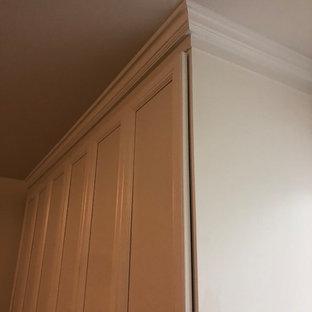 Immagine di un armadio o armadio a muro unisex tradizionale di medie dimensioni con ante con riquadro incassato, ante bianche, pavimento in ardesia e pavimento nero