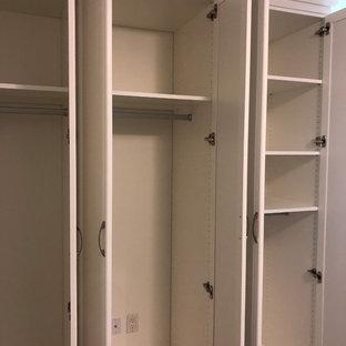 トロントの中サイズの男女兼用トラディショナルスタイルのおしゃれな壁面クローゼット (落し込みパネル扉のキャビネット、白いキャビネット、スレートの床、黒い床) の写真