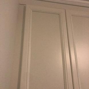 Esempio di un armadio o armadio a muro unisex tradizionale di medie dimensioni con ante con riquadro incassato, ante bianche, pavimento in ardesia e pavimento nero