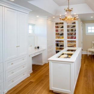 Ejemplo de vestidor de mujer, costero, grande, con armarios con paneles empotrados, puertas de armario blancas, suelo de madera en tonos medios y suelo marrón