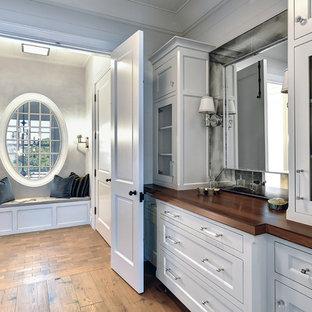 Immagine di uno spazio per vestirsi unisex costiero con ante di vetro, ante bianche e pavimento in legno massello medio