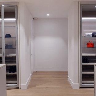 Foto de armario vestidor unisex, moderno, extra grande, con armarios tipo vitrina, puertas de armario blancas, suelo de madera clara y suelo beige