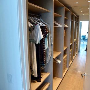 Foto de armario vestidor unisex, costero, con armarios con paneles lisos, puertas de armario de madera clara y suelo de madera oscura