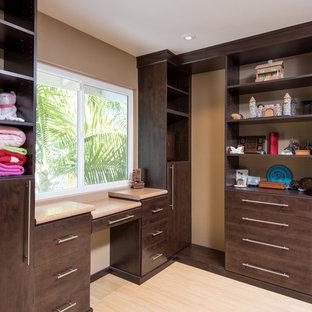 Idée de décoration pour un très grand dressing asiatique neutre avec un placard à porte shaker, des portes de placard en bois sombre et un sol en bois clair.