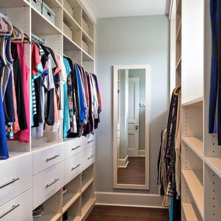 Inspiration för ett mellanstort maritimt walk-in-closet för kvinnor, med släta luckor, vita skåp och mörkt trägolv