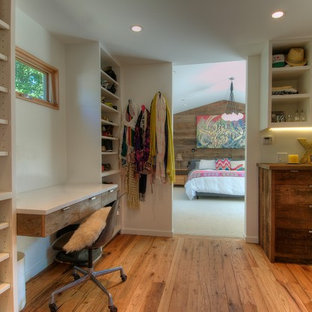 Photo of a midcentury women's dressing room in San Francisco with open cabinets, white cabinets and medium hardwood floors.