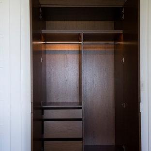 Foto de armario unisex, exótico, pequeño, con armarios con paneles lisos, puertas de armario de madera en tonos medios, suelo de madera en tonos medios y suelo marrón